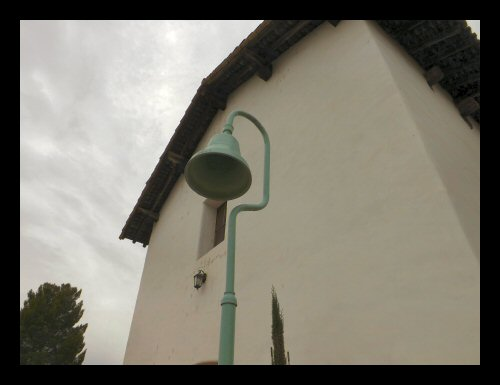 An El Camino Real marker bell in front of Mission San Miguel in San Luis Obispo County