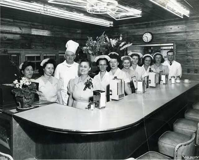 An early photo of the interior of the dining cars with the staff