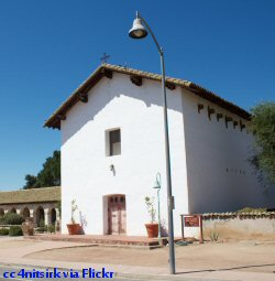 The east facing side of the church at Mission San Miguel. The sun enters through the window above the door.