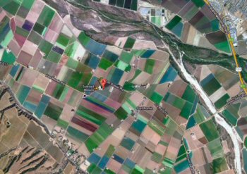 Mission Soledad in a mosaic of green fields