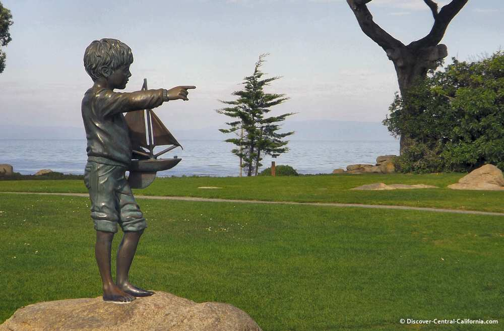 Statue of a boy with a sailboat pointing out to sea