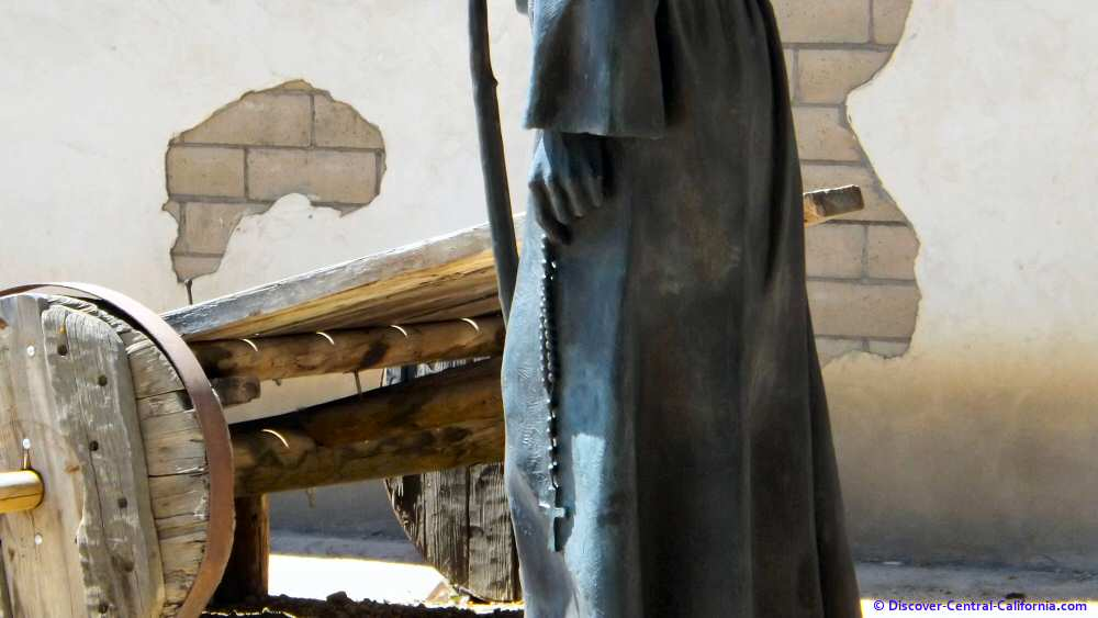 Detail of Serra statue and cart at Mission San Miguel