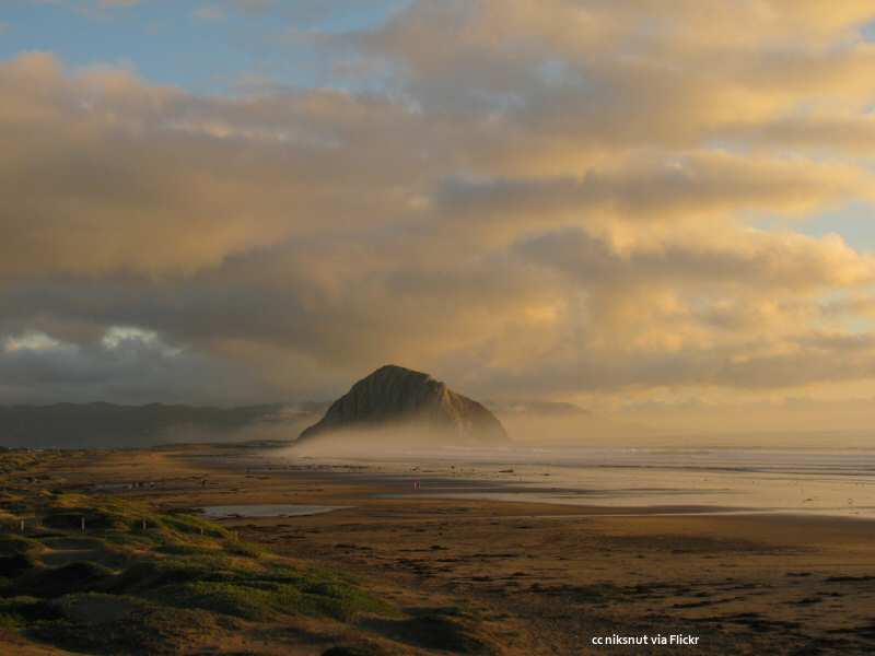 Light fog wraps around Morro Rock at sunset. Taken from North Point park.